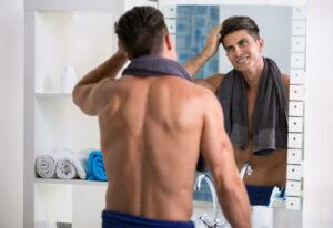 Uomo che si specchia e si tocca i capelli.