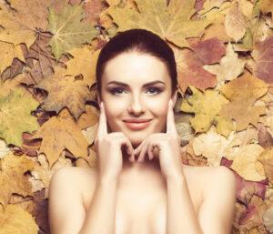 Donna dal viso curato con sfondo di foglie autunnali.